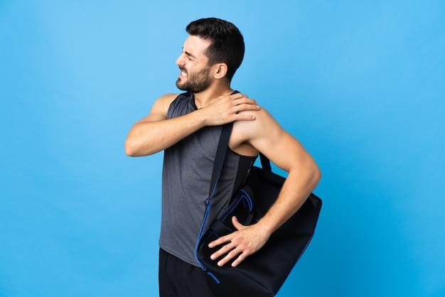 Jonge sportman met sporttas geïsoleerd op blauw die lijdt aan pijn in de schouder omdat hij zich heeft ingespannen