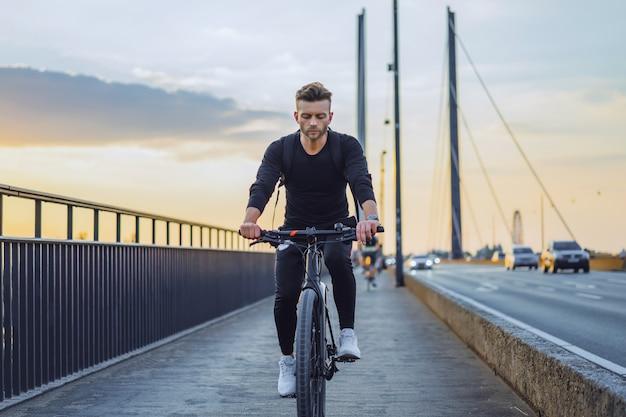 Jonge sportman op een fiets in een europese stad. sporten in stedelijke omgevingen.