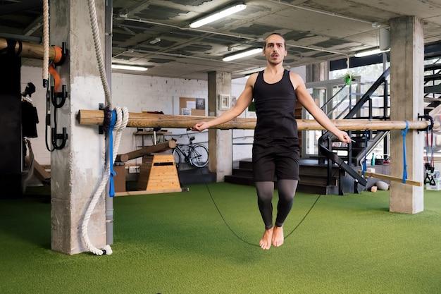 Jonge sportman training door touwtjespringen in de sportschool