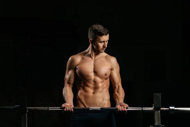 Jonge sportman traint de biceps in de sportschool tegen een donkere achtergrond