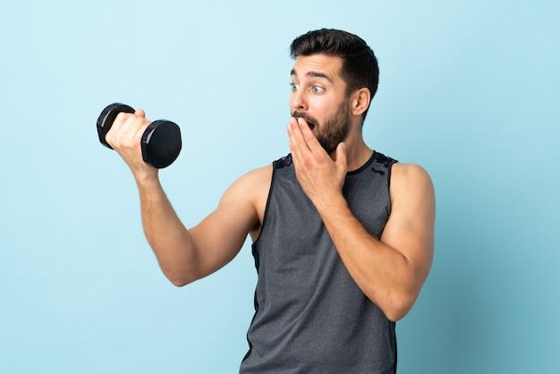 Jonge sportmens die met baard gewichtheffen met verrassing en geschokte gelaatsuitdrukking maken