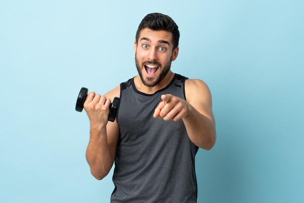 Jonge sportmens die met baard gewichtheffenpuntenvinger naar u met een zekere uitdrukking maakt