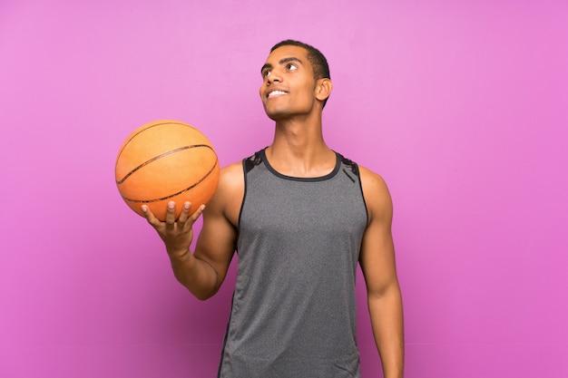 Jonge sportmens die met bal van basketbal over geïsoleerde purpere muur terwijl het glimlachen omhoog kijken