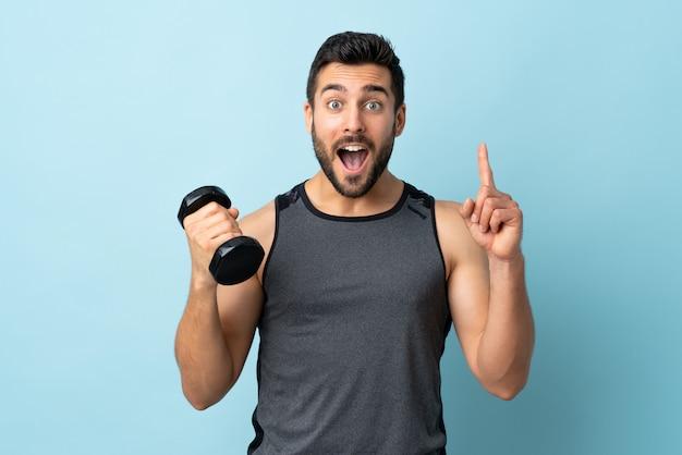 Jonge sportmens met baard die gewichtheffen het benadrukken van een groot idee maken