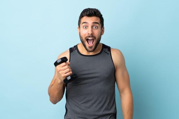 Jonge sportmens met baard die gewichtheffen met verrassing en geschokte gelaatsuitdrukking maken