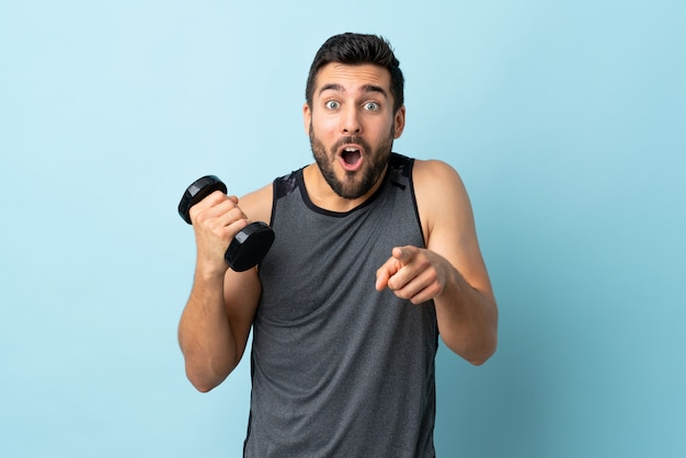 Jonge sportmens met baard die verrast gewichtheffen maken en voorzijde richten