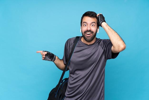 Jonge sportmens met baard over geïsoleerde blauwe muur die en vinger aan de kant wordt verrast verrast
