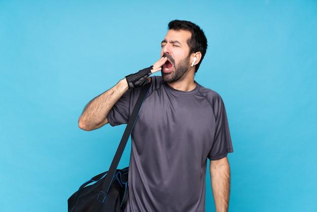 Jonge sportmens met baard over geïsoleerde geeuw en behandelend wijd open mond met hand
