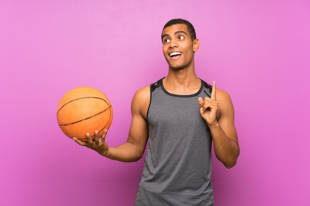 Jonge sportmens met bal van basketbal over geïsoleerde purpere muur die de oplossing van plan zijn te realiseren terwijl het opheffen van een vinger