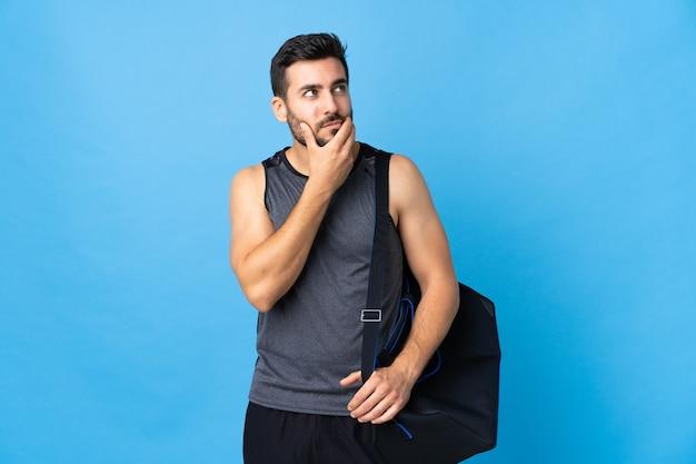Jonge sportmens met sporttas die op blauw wordt geïsoleerd met twijfels en met verwarde gezichtsuitdrukking