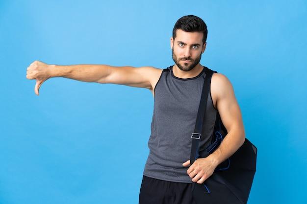 Jonge sportmens met sporttas die op blauwe achtergrond wordt geïsoleerd die duim met negatieve uitdrukking toont