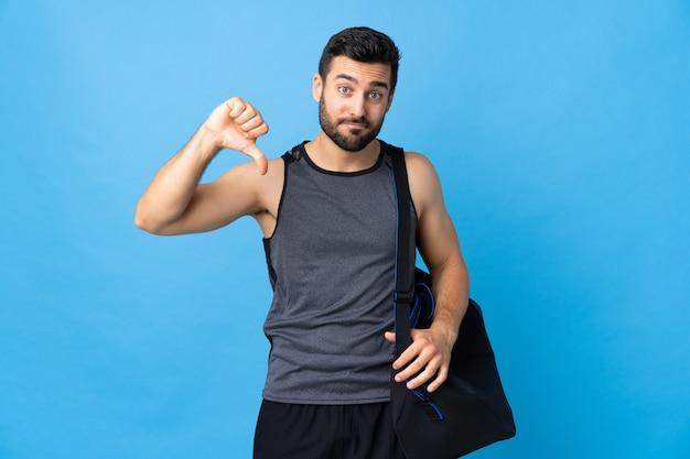 Jonge sportmens met sporttas die op blauwe duim met neer negatieve uitdrukking wordt geïsoleerd