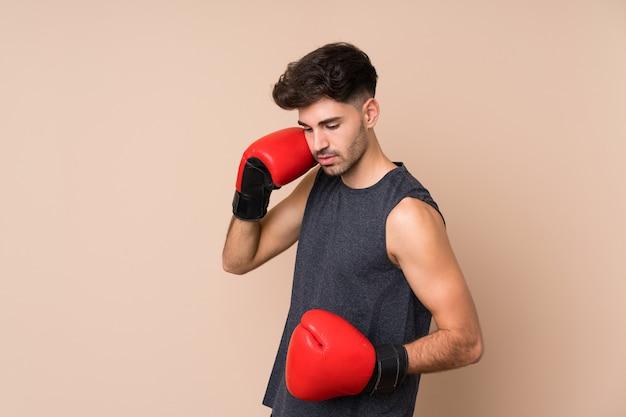 Jonge sportmens over geïsoleerd met bokshandschoenen