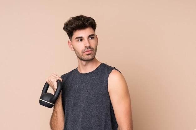 Jonge sportmens over geïsoleerde muur die gewichtheffen met kettlebell maakt