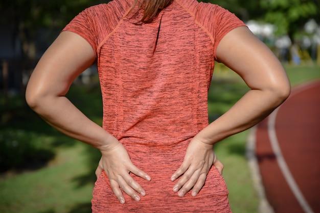 Jonge sportvrouw die aan rugpijn lijdt
