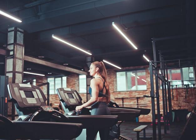 Jonge sportvrouw die cardiotraining op tredmolen doet. draait op loopband in de sportschool.