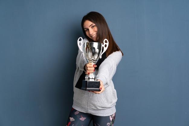 Jonge sportvrouw die een trofee houdt