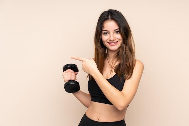 Jonge sportvrouw die gewichtheffen geïsoleerd op beige muur maken die vinger aan de kant richten