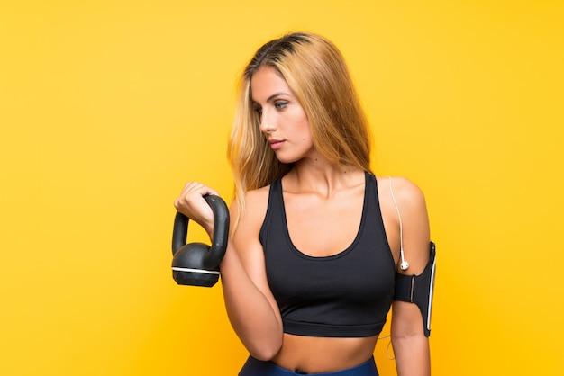Jonge sportvrouw die gewichtheffen met kettlebell over geïsoleerde gele muur maakt
