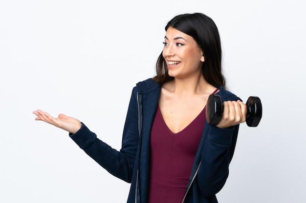 Jonge sportvrouw die gewichtheffen over geïsoleerde witte muur met verrassingsgelaatsuitdrukking maken