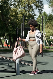 Jonge sportvrouw die haar tas op sportfaciliteiten zet