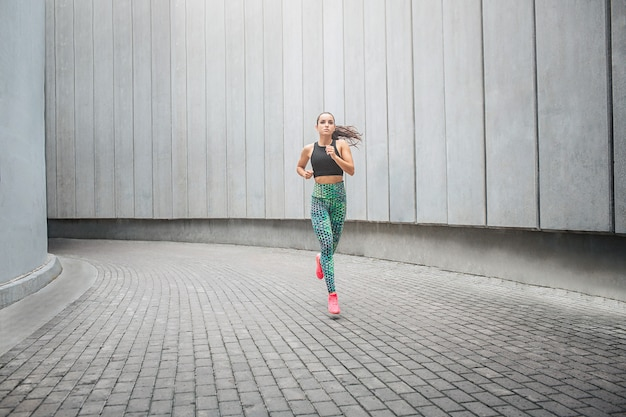 Jonge sportvrouw die in gang loopt
