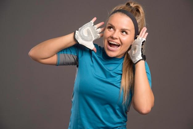 Jonge sportvrouw die luid teken maakt.