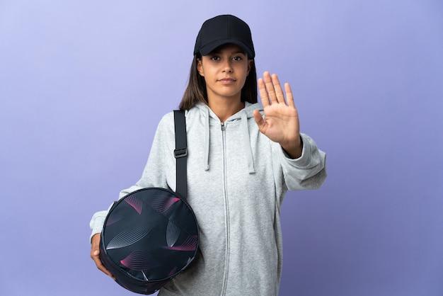 Jonge sportvrouw die met sporttas stopgebaar maakt