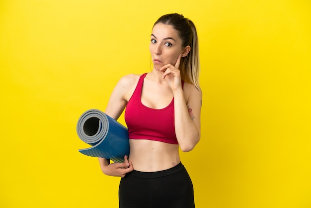 Jonge sportvrouw die naar yogalessen gaat terwijl ze een mat vasthoudt en een idee denkt