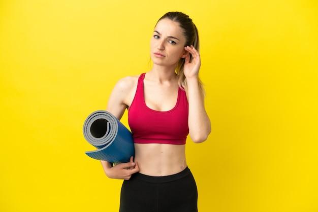 Jonge sportvrouw die naar yogalessen gaat terwijl ze een mat vasthoudt en twijfelt