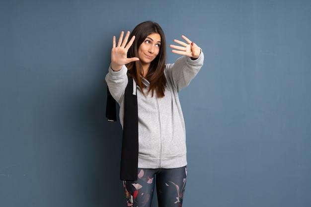 Jonge sportvrouw die negen met vingers telt