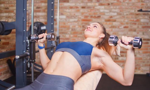Jonge sportvrouw die oefeningen met domoren in gymnastiek doen