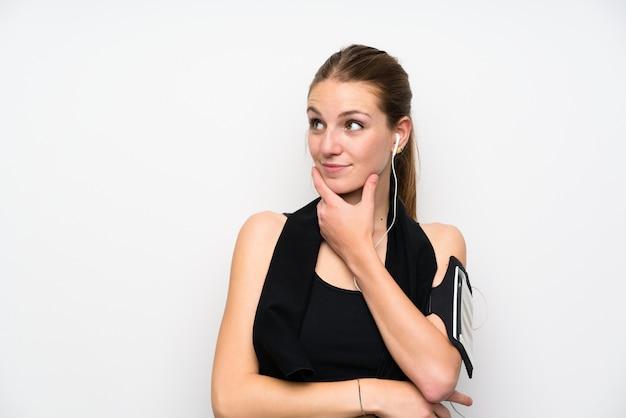 Jonge sportvrouw die over geïsoleerde witte muur een idee denkt
