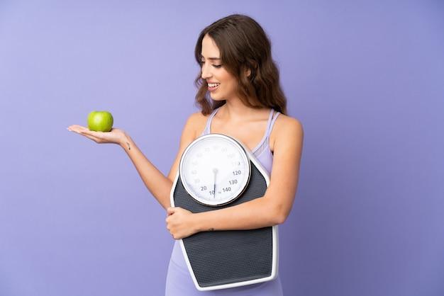Jonge sportvrouw die over purpere muur een wegende machine houdt terwijl het kijken een appel
