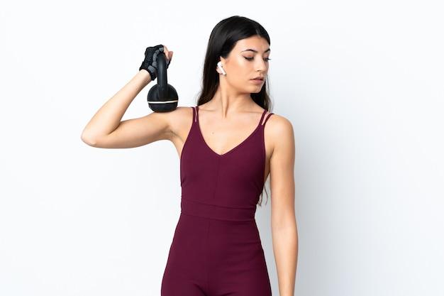 Jonge sportvrouw die over witte muur gewichtheffen met kettlebell maakt