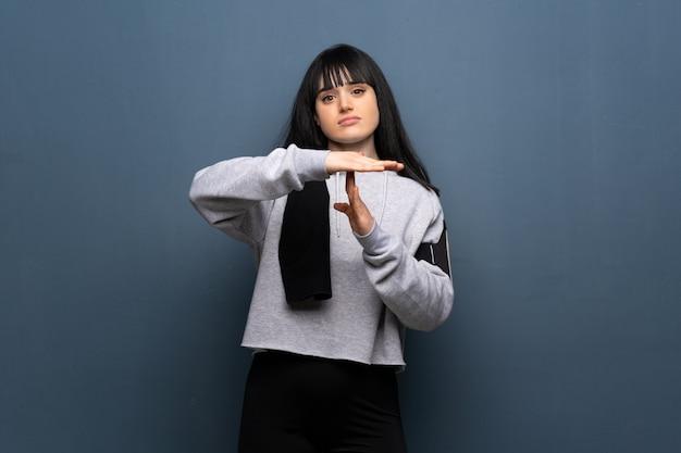 Jonge sportvrouw die tijd opmaken gebaar