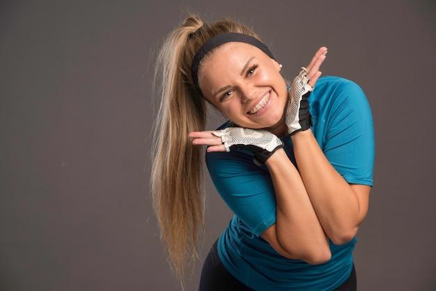 Jonge sportvrouw die vrolijk gezicht maakt.