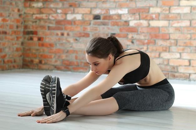 Jonge sportvrouw die zich uitstrekt