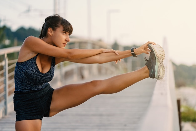 Jonge sportvrouw doen die zich in openlucht op een brug in de ochtend uitrekken