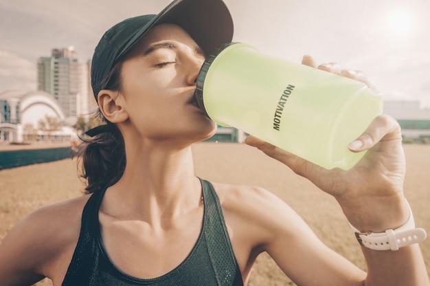 Jonge sportvrouw drinkt water na het joggen. geschiktheidsconcept.
