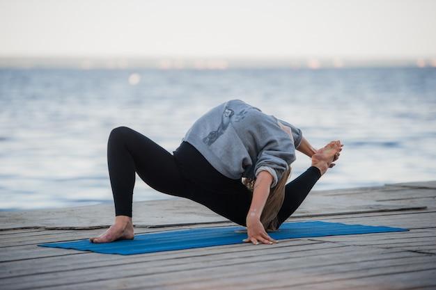 Jonge sportvrouw het beoefenen van yoga op het strand