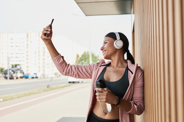 Jonge sportvrouw in draadloze koptelefoon glimlachend in de camera terwijl ze selfie portret maakt op mobiele ph...