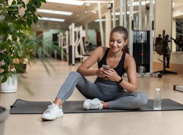 Jonge sportvrouw in sportkleding die smartphone gebruiken terwijl het zitten op mat in de gymnastiek. trainingspauze. gezonde levensstijl concept