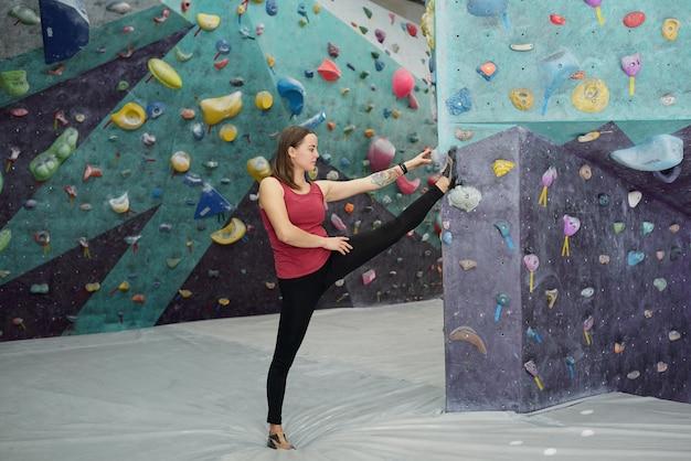 Jonge sportvrouw in zwarte leggings en kastanjebruin vest die zich door muur bevindt en één been voor zich gestrekt en opgeheven houdt