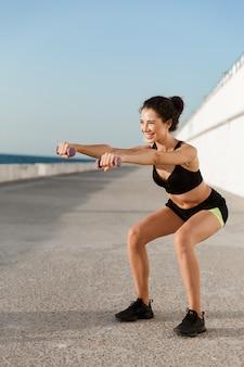 Jonge sportvrouw maakt oefeningen met halters buiten op het strand.