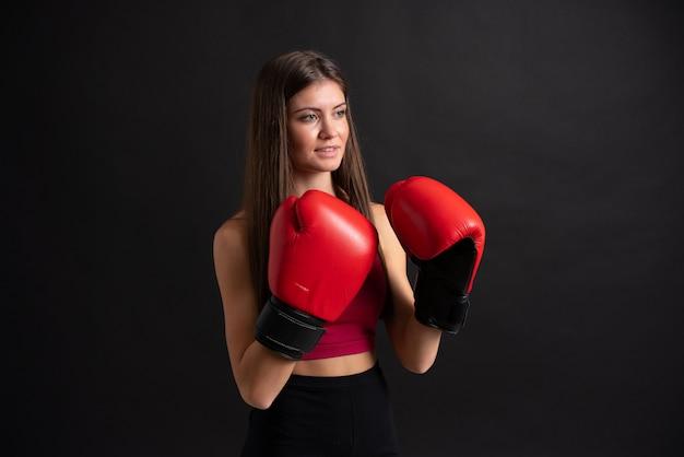 Jonge sportvrouw met bokshandschoenen over geïsoleerde zwarte
