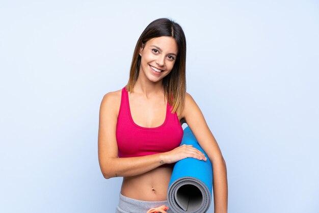 Jonge sportvrouw met een mat en het glimlachen