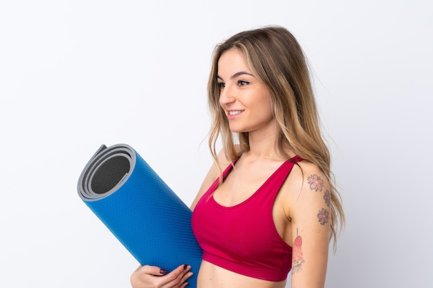 Jonge sportvrouw met een mat