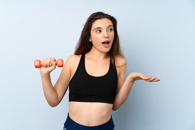 Jonge sportvrouw met gewichtheffen over geïsoleerde blauwe muur met verrassingsgelaatsuitdrukking