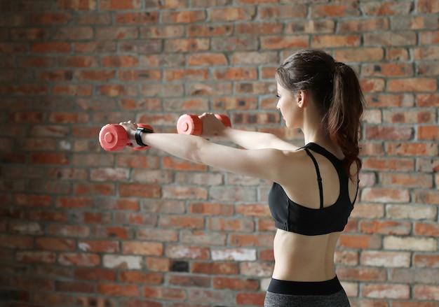 Jonge sportvrouw met halters